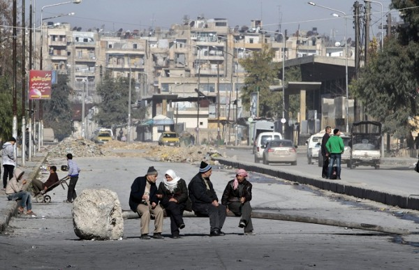 Men sit in middle of the road in Aleppo, Syria