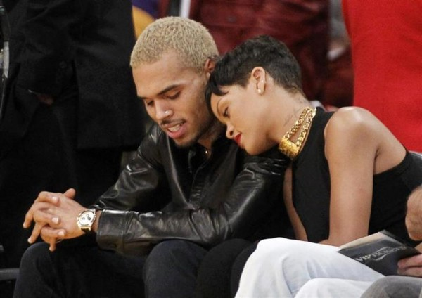Recording artist Rihanna leans her head on Chris Brown as they sit together courtside at the NBA basketball game between the New York Knicks and Los Angeles Lakers in Los Angeles December 25, 2012.