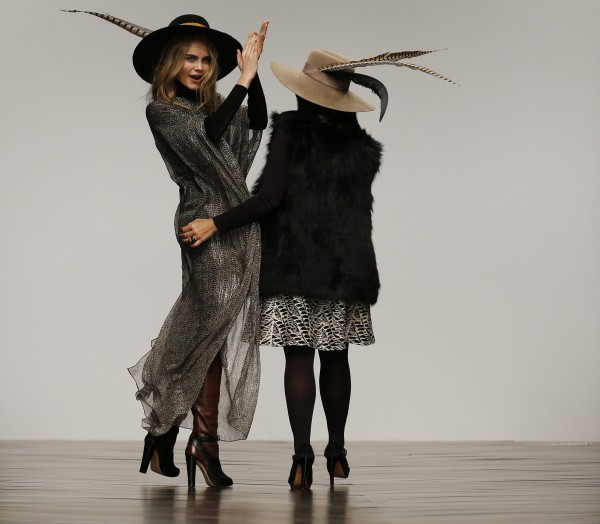 Issa designer Daniella Helayel (R), with model Cara Delevingne, accepts applause from guests after presenting the Issa Autumn/Winter 2013 collection during London Fashion Week, February 16, 2013.