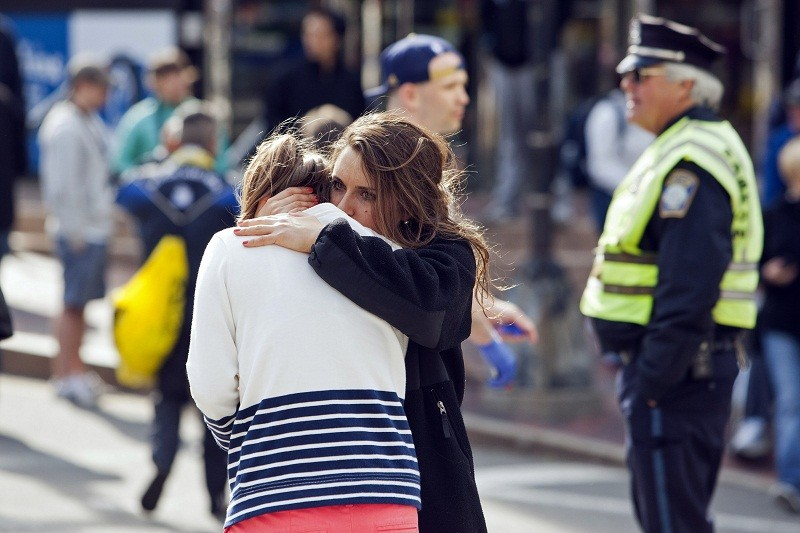 A woman comforts another, who appears to have suffered an injury to her hand, after explosions interrupted the 117th Boston Marathon in Boston, Massachusetts April 15, 2013. Two people were killed and