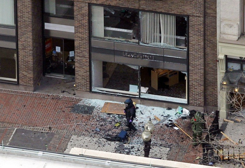 A man in a bomb-disposal suit investigates the site of an explosion which went off on Boylston Street during the 117th Boston Marathon in Boston, Massachusetts April 15, 2013. Two explosions hit the B