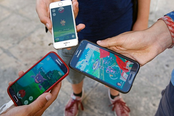Kids show the screen of their smartphone with Nintendo Co.'s Pokemon Go augmented-reality game at the Trocadero in front of the Eiffel tower on September 8, 2016 in Paris, France.