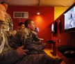U.S Air Force Staff Sargent Ryan Propst (center) plays 'Call of Duty' video game at the United Service members Organization (USO) lounge at Kandahar Air Field (KAF) December 8, 2010.