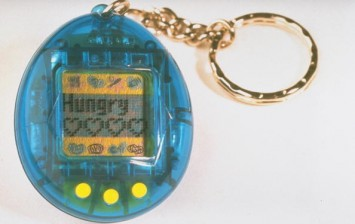Tamagotchis, a virtual pet that grows from chick to adult on a minicomputer screen in 10 days only w. proper care from button-pressing owner, made by the Japanese firm Bandai.