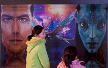 Moviegoers walk past an advertisement for the film 'Avatar' at a theater in Beijing, China, on Wednesday, Jan. 20, 2010.