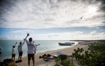 The crew of Team Vestas Wind wave to the plane to say thanks for dropping supplies to the island following the grounding of the boat on a reef on December 03, 2014 in Mauritius.