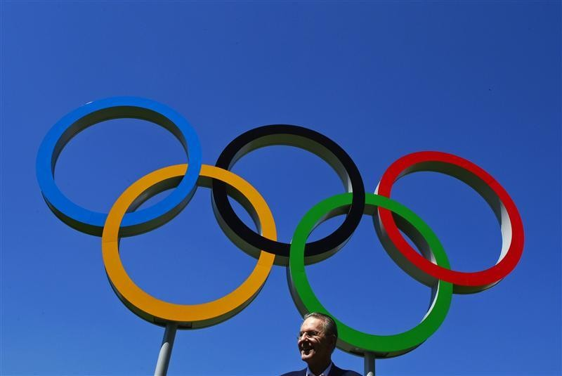 President of the International Olympic Commission, Jacques Rogge, stands near Olympic rings during a tour of the Athletes Village at the Olympic Park in Stratford in east London July 23, 2012.