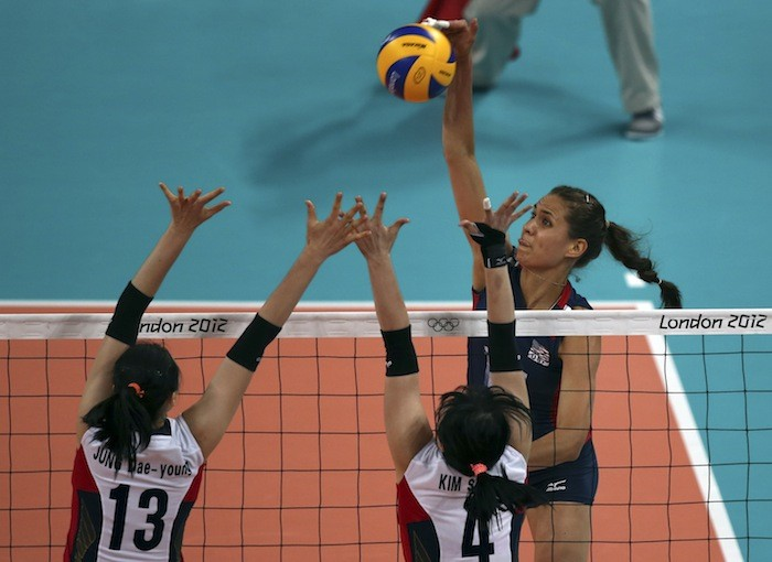Logan Tom of the U.S. spikes the ball against South Korea's Jung Dae-young (L) and captain Kim Sa-nee during their women's Group B volleyball match at the London 2012 Olympic Games at Earls Court in L
