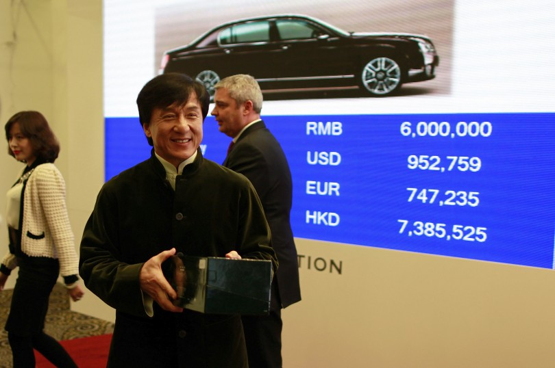 Kung Fu superstar Jackie Chan holds a packed model of a Bentley 666 in front of a board showing the car and its price, after having the car auctioned for charity in Beijing, November 19, 2012. Chan sa