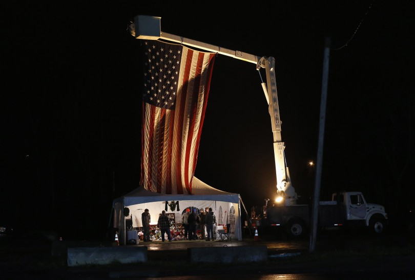 People stand by a makeshift memorial with a U.S. flag, honoring the victims of the Sandy Hook Elementary School shooting, in Newtown, Connecticut December 17, 2012.