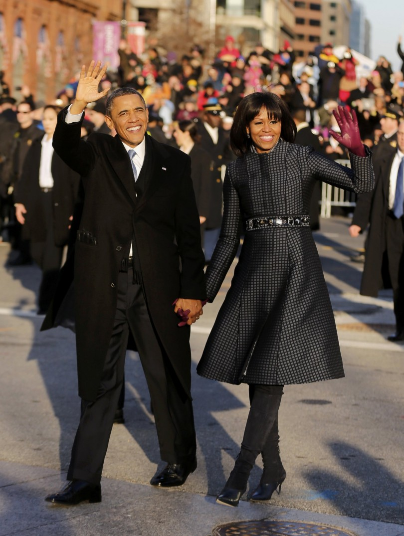 U.S. President Barack Obama and first lady Michelle Obama walk and wave after emerging from the presidential limousine during the inaugural parade from the Capitol to the White House in Washington, Ja