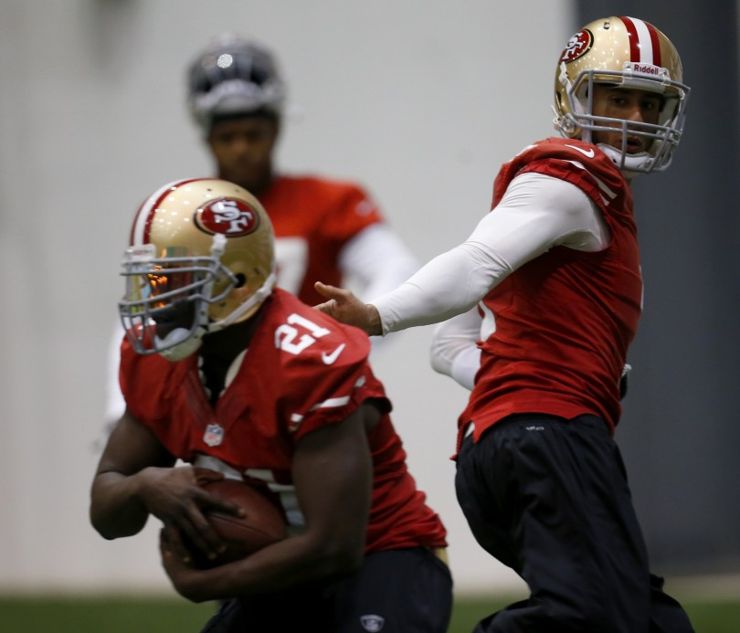 San Francisco 49ers quarterback Colin Kaepernick (R) hands off to running back Frank Gore (L) during practice for the Super Bowl in New Orleans, January 30, 2013.